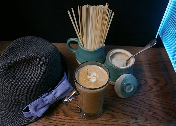 A coffee drink, sugar dispenser and a jar of stirrers on a table