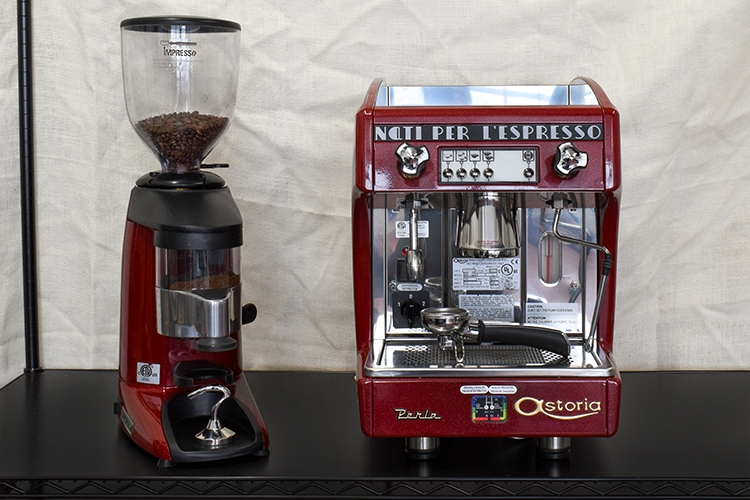 A red espresso grinder and a red espresso machine with white background