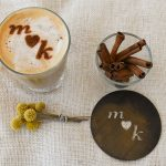 A latte with initials stenciled on top, a glass of cinnamon sticks, the stencil and dried flowers on top of white table cloth